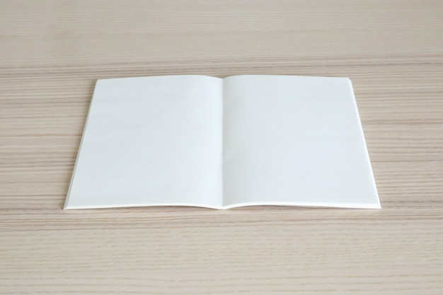 Blank open paper book on wooden table