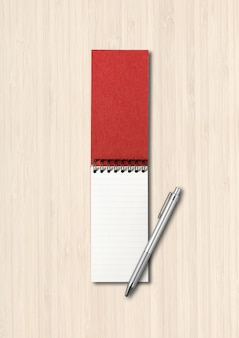 Пустой открытый спиральный блокнот и макет ручки, изолированные на белом деревянном фоне