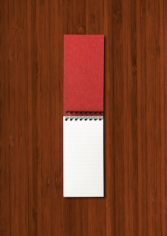 Blank open spiral notebook mockup isolated on dark wood background