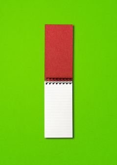 Blank open spiral notebook mockup isolated on green