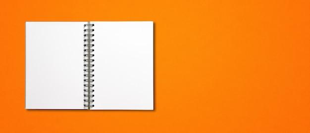 オレンジ色の水平バナーに分離された空白のオープンスパイラルノートブックモックアップ