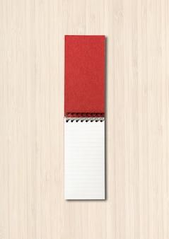 白い木製で隔離の空白のオープンスパイラルノートブックモックアップ