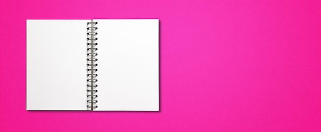 Blank open spiral notebook mockup isolated on pink horizontal surface