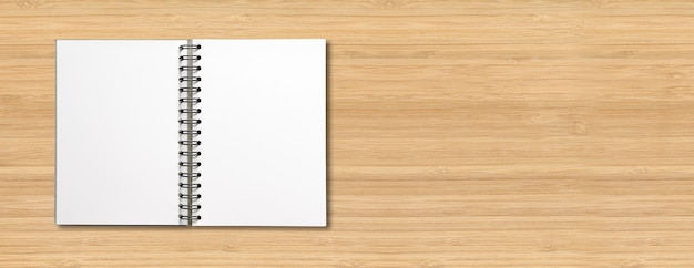 Blank open spiral notebook mockup isolated on wooden horizontal banner