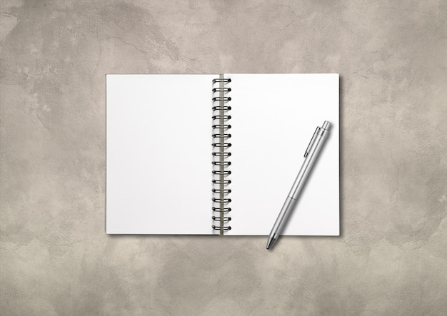 Blank open spiral notebook mockup and pen isolated on concrete background