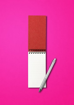 Blank open spiral notebook and pen mockup isolated on pink