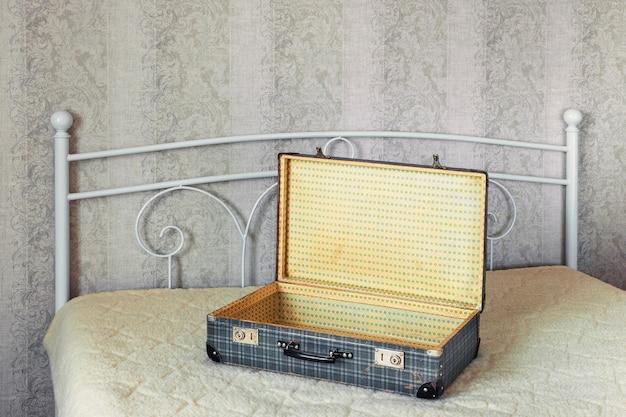 Пустой открытый чемодан, стоящий на широкой кровати