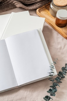 Пустая открытая книга, свечи и листья эвкалипта на белой кровати, плоская планировка