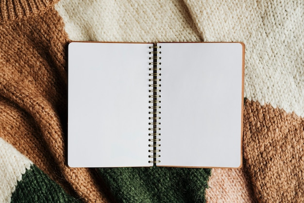 Blank opened notebook on a sweater