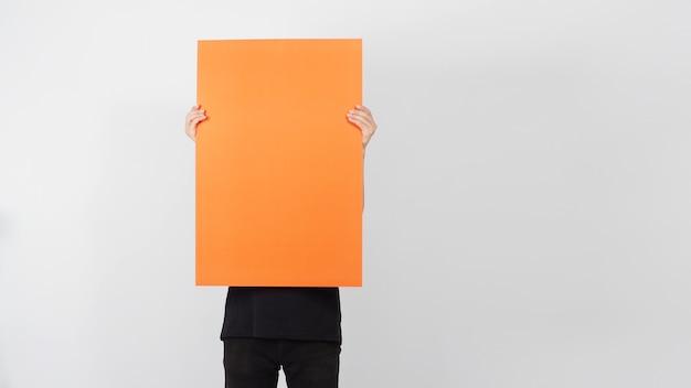 Пустая бумага оранжевого цвета в руке человека на белой предпосылке.