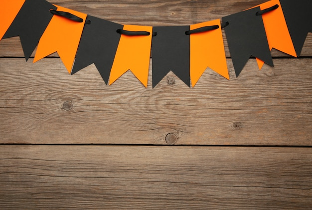 Blank and orange party flags for halloween decoration on grey background. top view