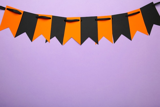 Blank and orange party flags for halloween decoration on violet background. top view