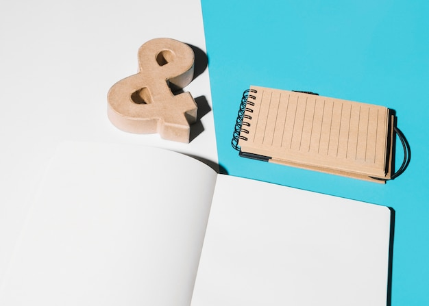 Blank page; ampersand symbol and spiral notepad on white and blue background