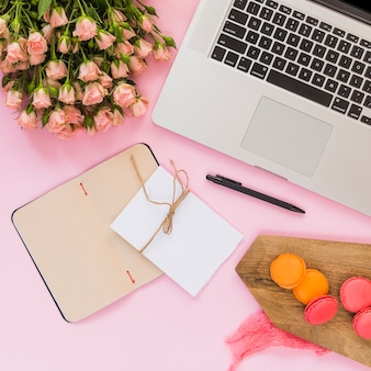 Blank page diary; card; pen; flower bouquet; laptop; pen and macaroons of chopping board