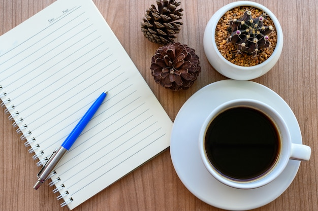 Blank page of note book with black coffee cup, cactus, pine cones on wooden table, flat lay