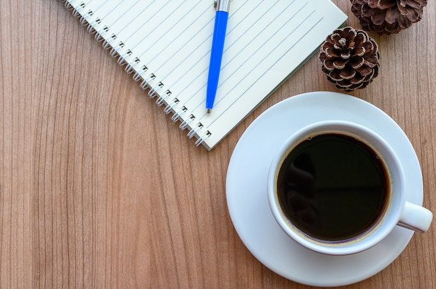 Blank page of note book with black coffee cup, pine cones on wooden table, flat lay