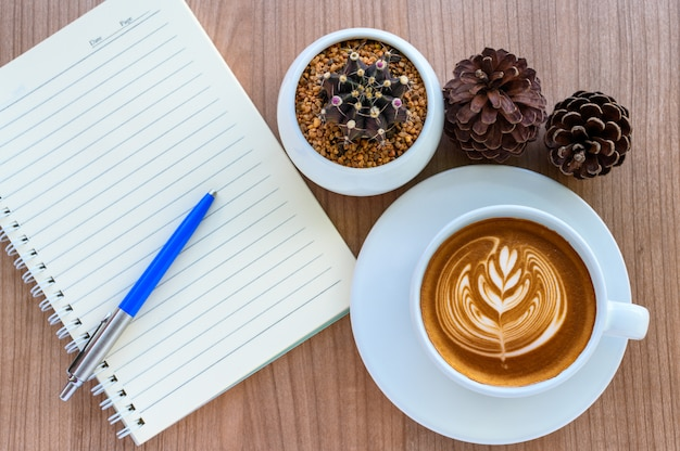 Blank page of note book with latte art coffee cup, cactus, pine cones on wooden table, flat lay