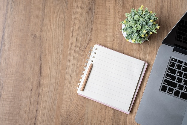 Blank page of notebook and laptop on wooden table