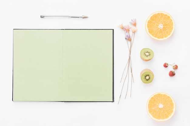 Blank page notebook; pen; dried flower; strawberry and halved fruits on white backdrop