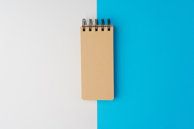 Blank page of notepad on blue nad white paper background