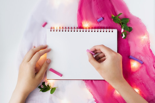 Blank page of open notebook and decor items on pink and white