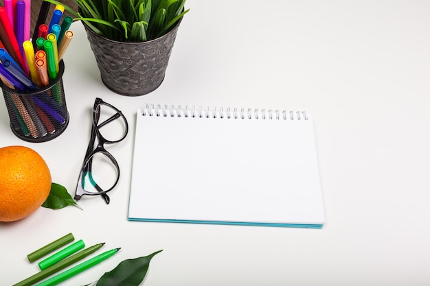 Blank page of spiral notepad on white table.
