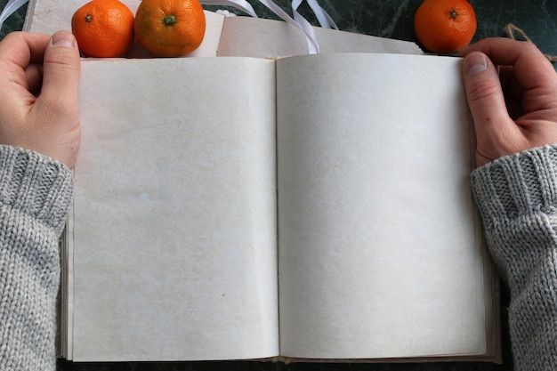 Blank pages opened vintage book on green marble countertop