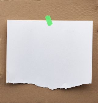 Blank paper ad with torn edges attached with a green velcro on a brown cardboard surface