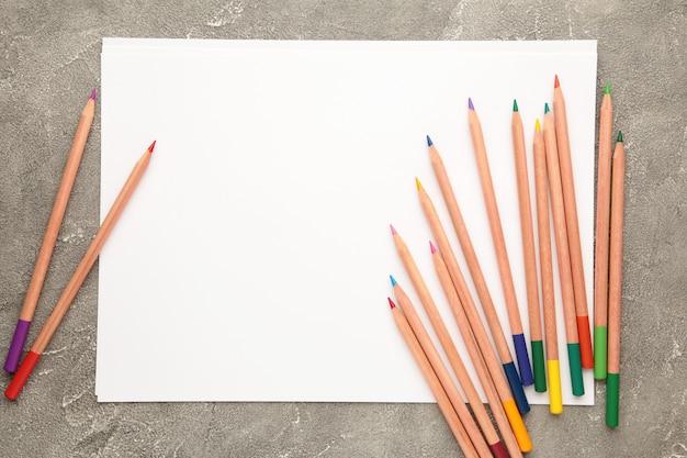 Чистый лист бумаги и красочные карандаши на сером.