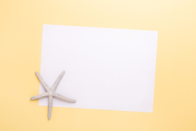 Чистый лист бумаги и морские звезды на желтом фоне. концепция планирования летних каникул и каникул - изображение