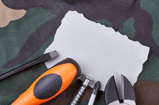 白紙と工具ペンチ、ドライバー、ネジ。仕事のドラフトを作成します。