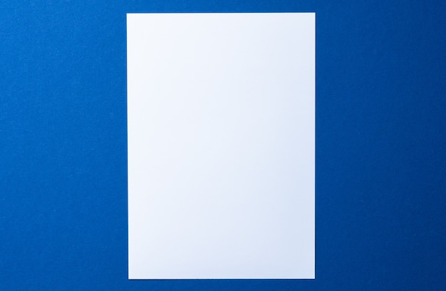 Blank paper on blue background top view