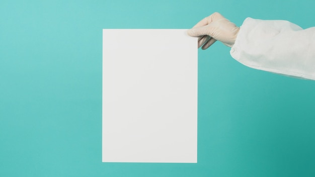 Чистый лист бумаги в руке женщины. она носит белые латексные перчатки и костюм из полипропилена на зеленой мятой или синем фоне тиффани.