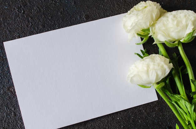 Blank paper and bouquet of white flowers
