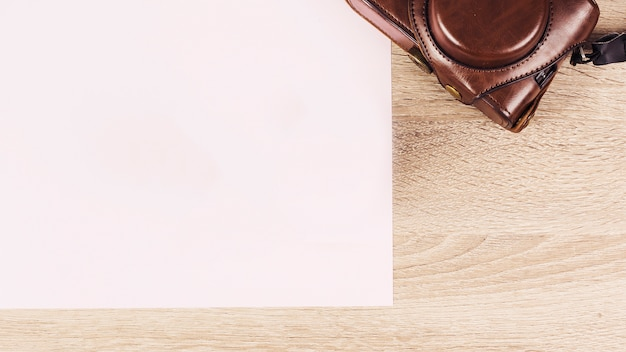 Blank paper in camera pouch on wooden background