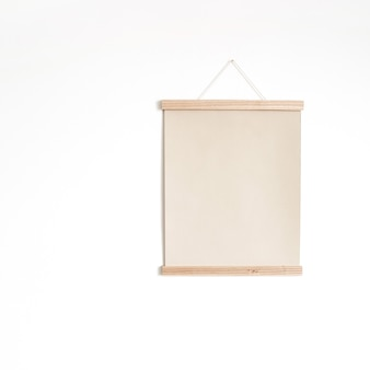 Плакат листа холста чистого листа бумаги на белой стене.