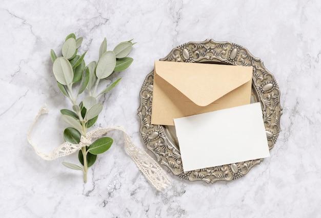 Пустая бумажная карточка и конверт с ветвями эвкалипта на винтажной тарелке на мраморном столе. макет карты