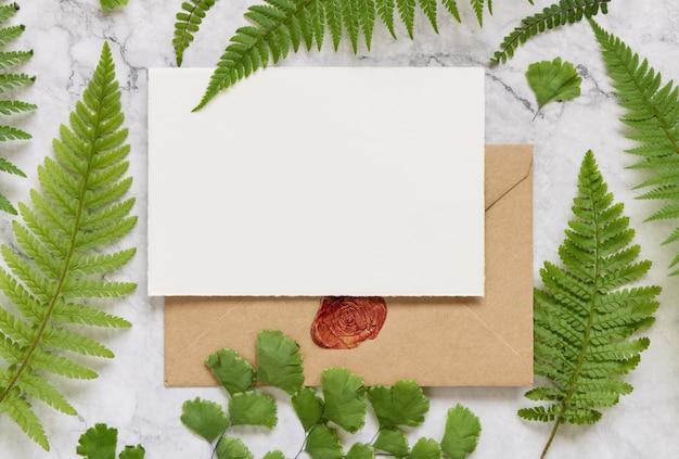 白い大理石のテーブルトップビューにシダの葉で飾られた白紙のカードと封印された封筒。グリーティングカードフラットレイと熱帯のモックアップシーン