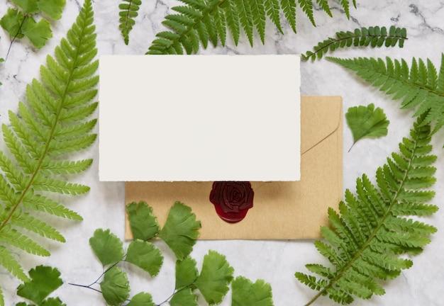 Пустая бумажная карточка и запечатанный конверт, украшенный листьями папоротника на белом мраморном столе. тропический макет сцены с плоской планировкой поздравительной открытки