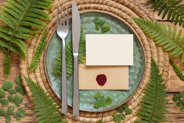 Пустая бумажная карточка и запечатанный конверт на сервировке стола, украшенной листьями папоротника на взгляд сверху деревянного стола. тропический макет сцены с плоской планировкой свадебной открытки