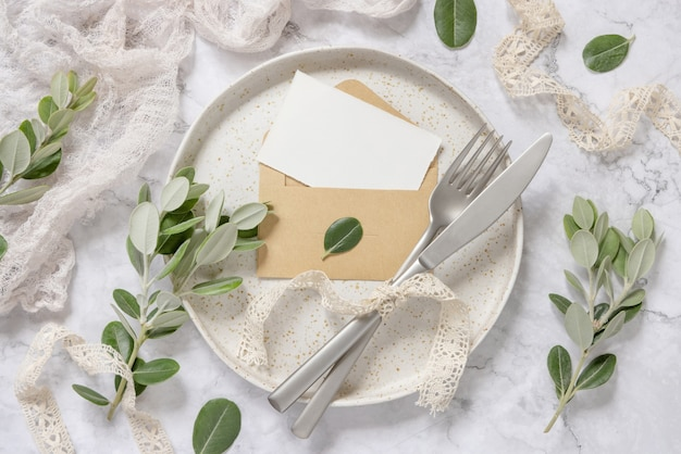 Blank paper card in envelope laying on white plate with fork and knife on marble table with eucalyptus branches and vintage ribbons around, top view. card mockup