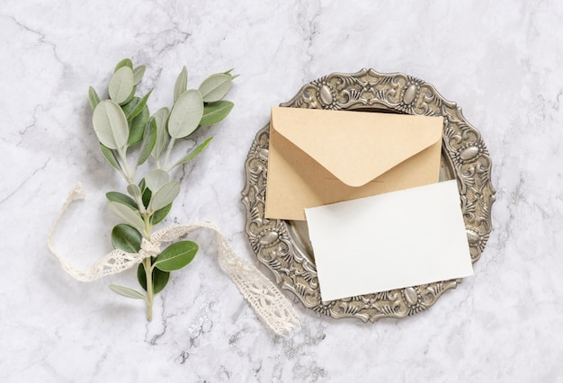 Blank paper card and envelope with eucalyptus branches on vintage plate on marble table top view. card mockup