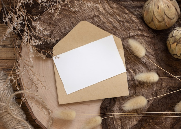 Blank paper card on envelope and wooden table with dried plants around, top view. boho mock-up scene with invitation card template