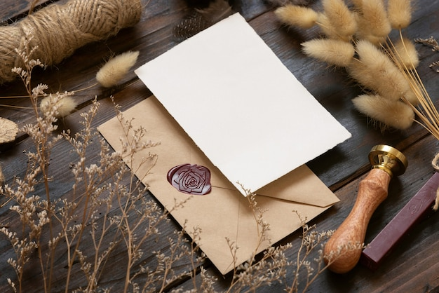 Blank paper card on envelope and wooden table with dried plants closeup
