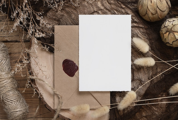 Blank paper card and envelope on a wooden table with dried plants
