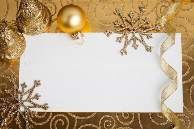 Пустая бумажная карточка оформлена елочными украшениями на золоте