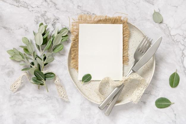 Пустая бумажная карточка, лежащая на белой тарелке с вилкой и ножом на мраморном столе с ветвями эвкалипта и старинными лентами вокруг, вид сверху. макет карты