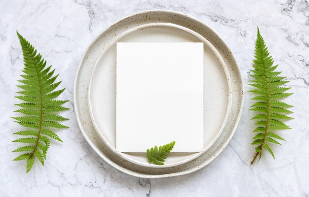 Blank paper card on laying on a plate on marble table with fern leaves around top view. tropical mock-up scene with invitation card flat lay