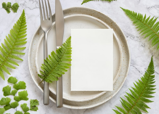 Blank paper card on laying on a plate with fork and knife on marble table with fern leaves around top view. tropical mock-up scene with invitation card flat lay