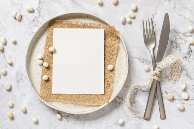 Blank paper card laying on sacking on white plate with fork and knife tied with vintage ribbons on marble table with little stones around, top view. card mockup